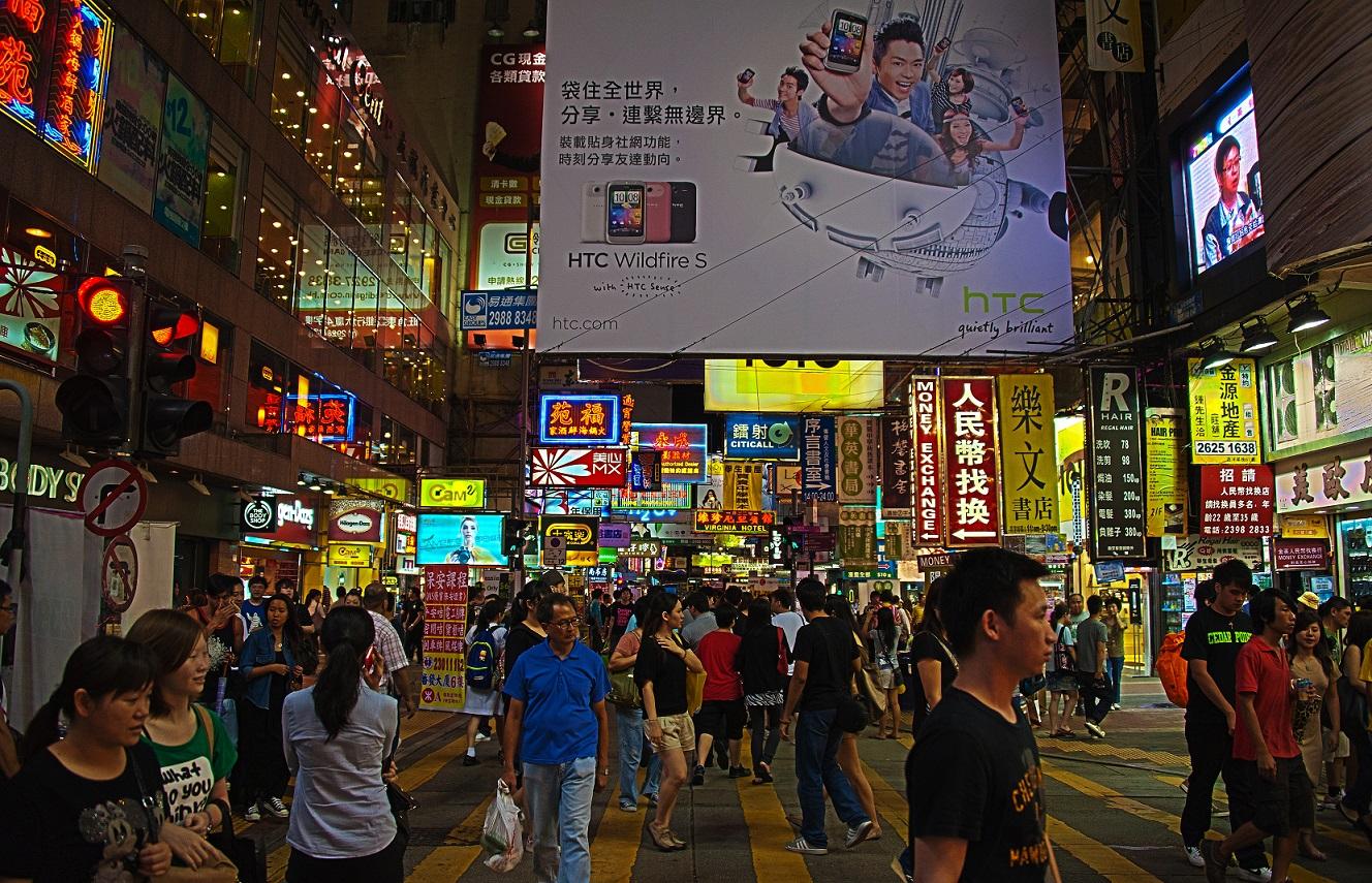A vida urbana das calçadas se revela sob a densidade de prédios de Kowloon, Hong Kong.
