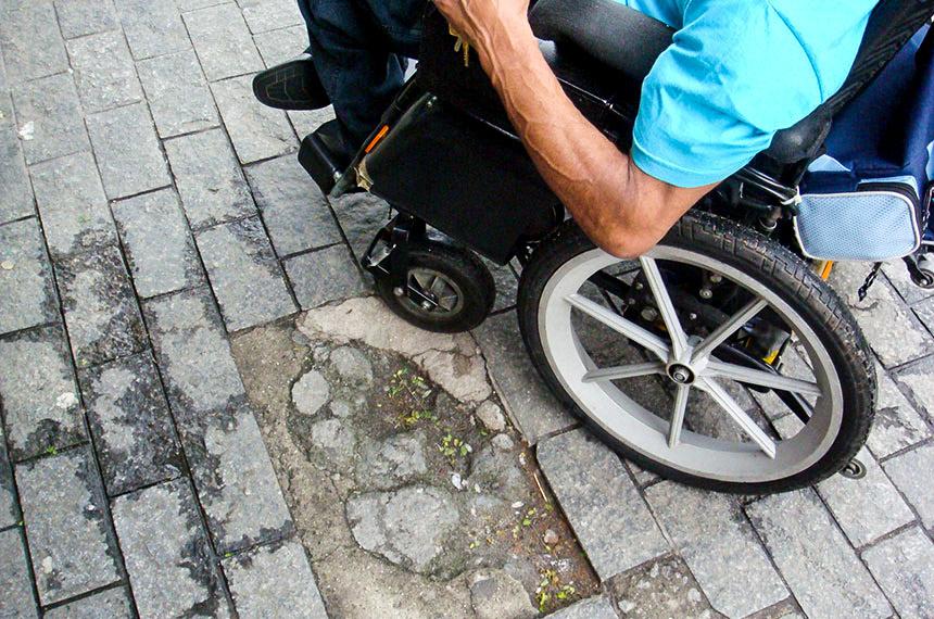 Calçada com piso inadequado para circulação de cadeirantes.